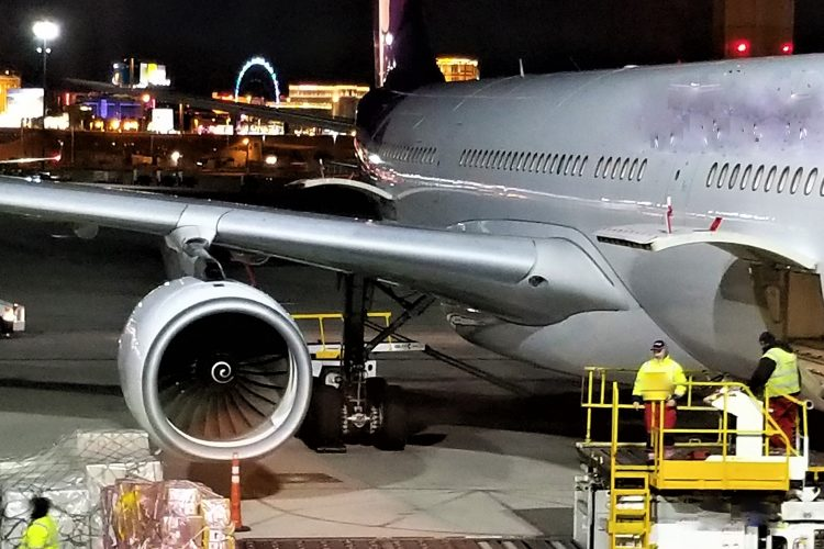 at-the-airport-cargo-handlers-on-the-tarmac-loading-cargo-pallets-of-supplies-into-the-cargo-hold-of_t20_xvgWx8